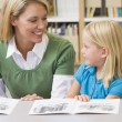 Kindergarten teacher helping student with reading skills — Stock fotografie