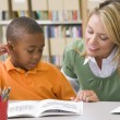 Kindergarten teacher helping student with reading skills — Stock Photo