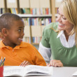 Kindergarten teacher helping student with reading skills — Stockfoto