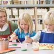 Stock Photo: Kindergarten teacher sitting with students in art class