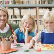 Kindergarten teacher sitting with students in art class — Stock Photo