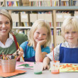 Kindergarten teacher sitting with students in art class — Stock Photo #4759788