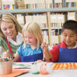 Kindergarten teacher sitting with students in art class — Stock Photo #4759791
