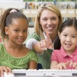 Stock Photo: Kindergarten teacher sitting with children at computer