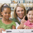 Kindergarten teacher sitting with children at computer — Stock Photo