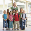 Kindergarten teacher standing with children in corridor — Stock Photo