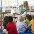 Kindergarten teacher reading to children in library -  