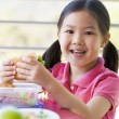 Stock Photo: Girl eating lunch at kindergarten