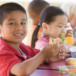 Kindergarten children eating lunch - Stock Photo