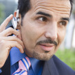 Stock Photo: Businessmusing bluetooth earpiece