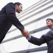 Businessmen shaking hands outside office building — Stock Photo #4759915
