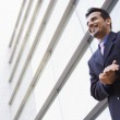 Businessman standing outside office building — Stock Photo