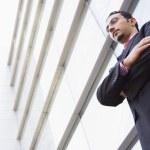 Businessman standing outside modern office — Stock Photo