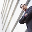 Businessman standing outside office block — Stock Photo #4759922
