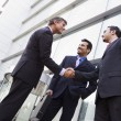 Business shaking hands outside office - Stok fotoğraf