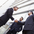 Group of businessmen shaking hands outside office — 图库照片