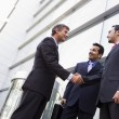 Group of businessmen shaking hands outside office — Stock Photo