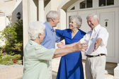 Senior couple greeting friends — Stock Photo