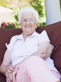Senior woman sitting on garden chair — Stockfoto