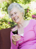 Senior woman enjoying glass of wine — Foto Stock