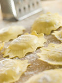 Uncooked Spinach and Ricotta Ravioli on a floured surface — Stock Photo