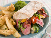 Steak and Roasted Pepper Ciabatta Sandwich with Spiced Potato We — Stock Photo