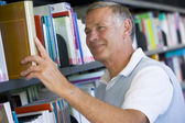 Senior man pulling a library book off shelf — Stock Photo