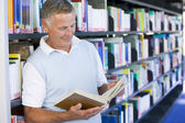 Senior man reading in a library — Foto Stock