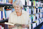 Senior woman reading in a library — Stockfoto