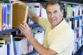 Man pulling a library book off shelf — Stock Photo