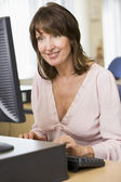 Middle aged woman working on a computer — Stock Photo