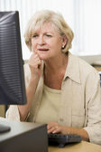 Confused woman frowning at computer monitor — Stock Photo