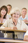 Senior woman listening to a university lecture — Stock Photo