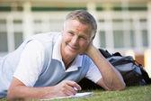 En man skriver anteckningar liggande på en campus gräsmatta — Stockfoto