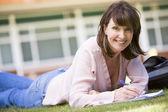 En kvinna skriver anteckningar liggande på en campus gräsmatta — Stockfoto