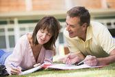 Un hombre y una mujer escribiendo notas mientras se está acostado en el césped del campus — Foto de Stock