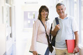 A man and woman with backpacks standing in a campus corridor — Stock Photo