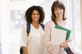 Two women with backpacks standing in a campus corridor — Foto Stock