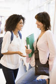 Two women students chatting in a campus corridor — Stock Photo