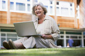 Senior woman using laptop on campus — Stock Photo