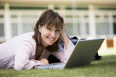 Woman using laptop on campus — Stock Photo