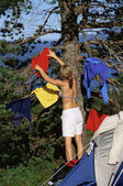 Young woman hanging out washing on a tree next to campsite — Stock Photo