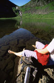 Young woman relaxing on rocks next to lake — Stock Photo