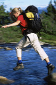 Hiker jumping from rock to rock while crossing river — Stok fotoğraf