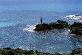 Jonge vrouw staande rotsen, uitzicht op zee — Stockfoto