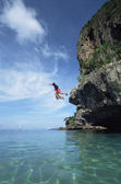 Couple jumping from cliffs into the sea — Stock Photo