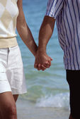 Couple walking on beach holding hands — Stock Photo