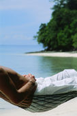 Midsection of man lying in hammock at beach — Stock Photo