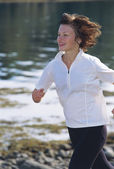 Young woman running along water's edge — Stock Photo