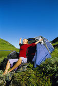 Young woman waking up next to tent — Stock Photo